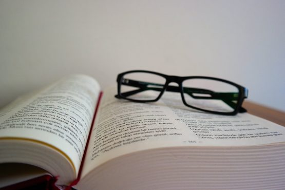 glasses lying on the opened book