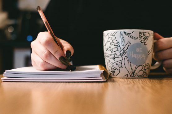 a girl writing in a notebook with a cup of tea next to her