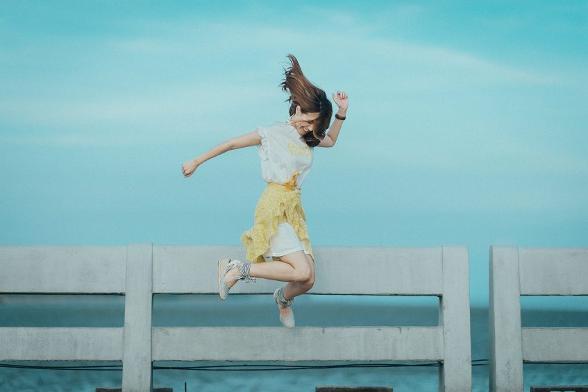 girl jumping next to a fence and a field