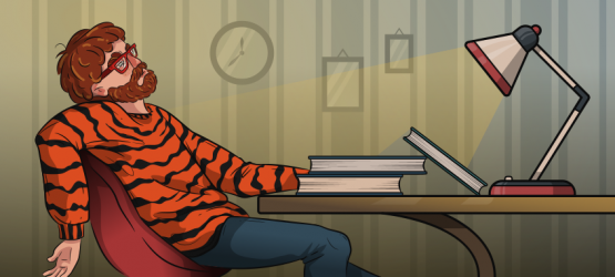 guy in a tiger sweater is sitting at the desk tired
