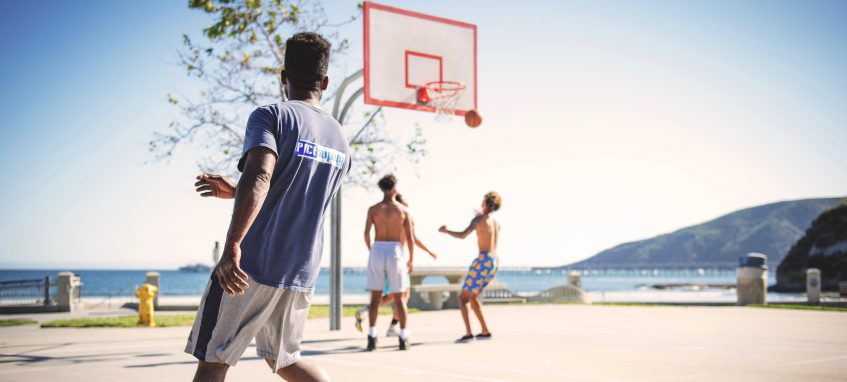 three guys play basketball outside