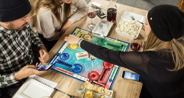three students are playing board games and drinking wine