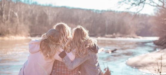 three women hug each other sitting at the river