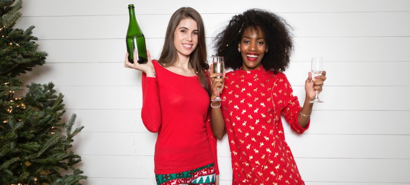 two girls with a bottle of champagne stand near a Christmas tree