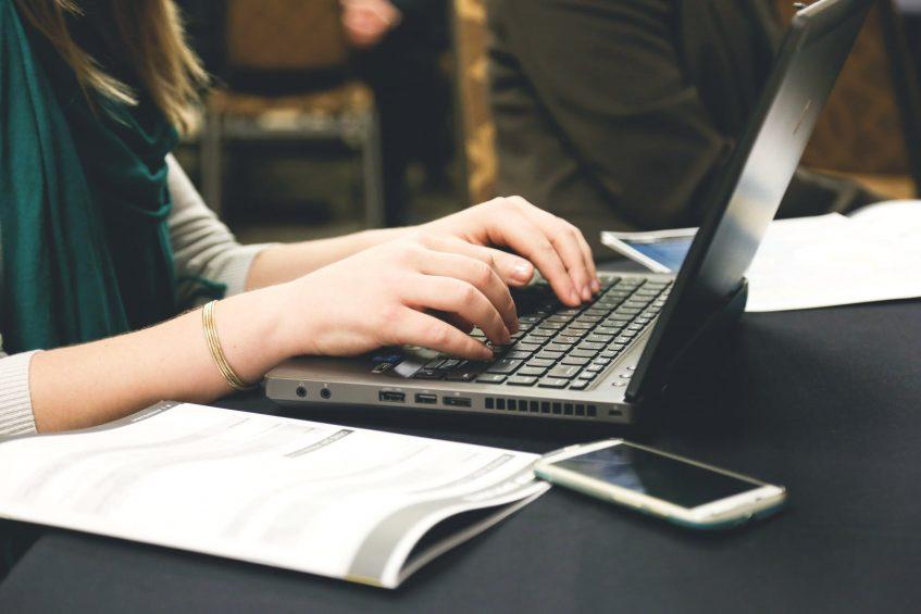 woman typing on laptop writing