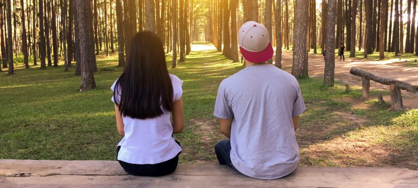 young couple sitting on the bench in the wood