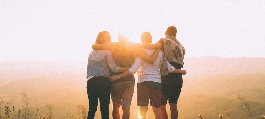 young people stand in a row, hug each other and look at sunset